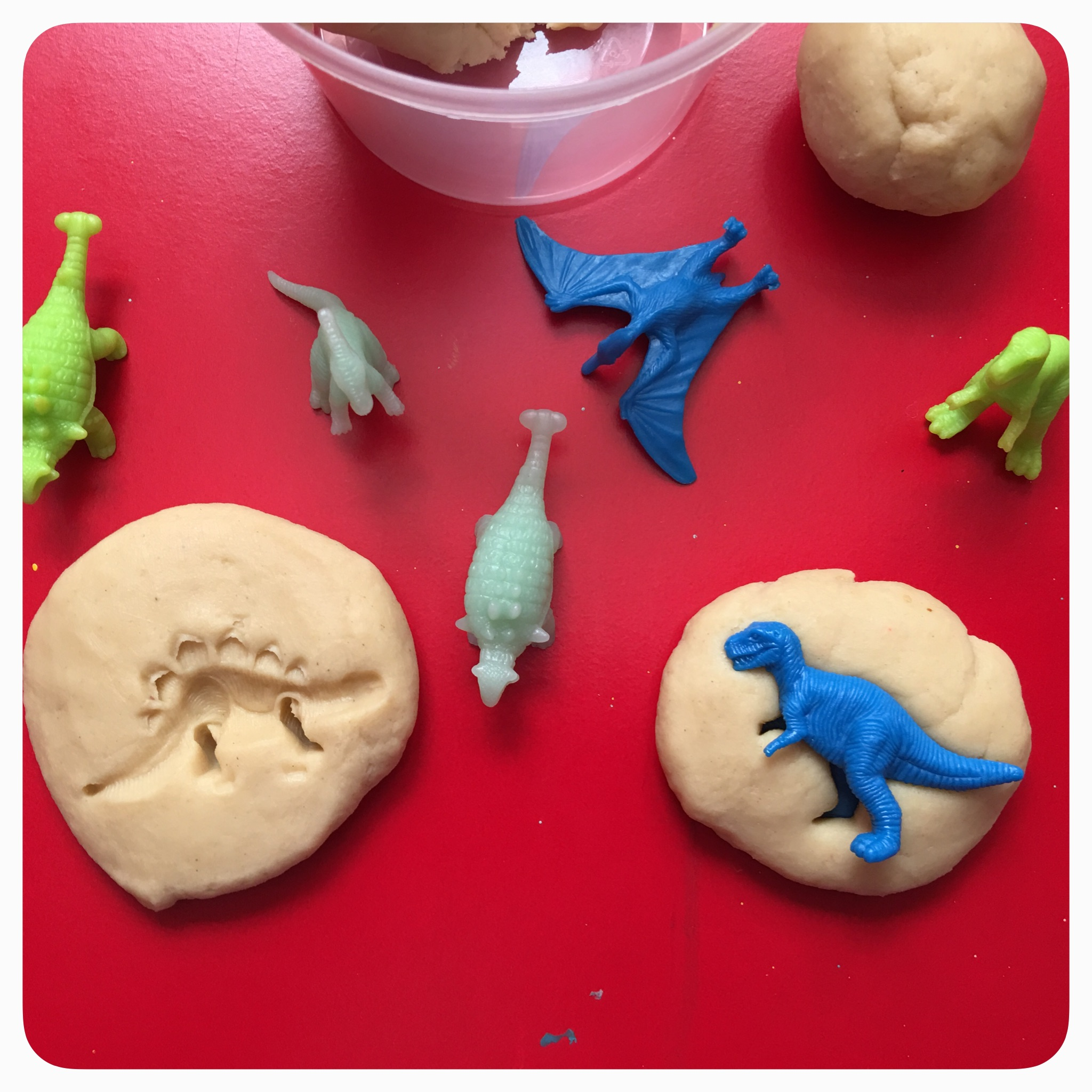 Creating simple play-dough invitations to play for exploring Dinosaurs.
